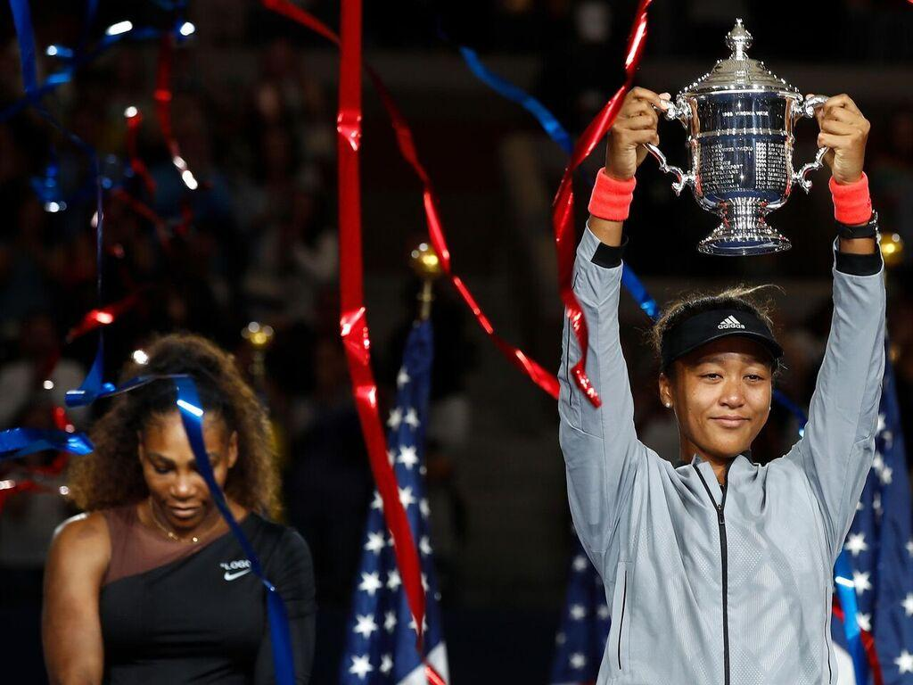Naomi Osaka (right) lifts up her new trophy for the U.S. Open as Serena Williams (left) hangs her head after the day's struggles and frustrations. Source Kut.com