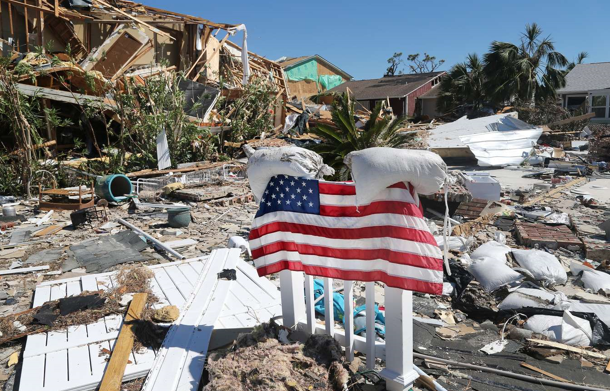 Flag being held up by sacks of sand amongst the destruction that Hurricane Michael left. Source: https://www.tampabay.com/photos/2018/10/13/hurricane-michael-in-photos-surveying-michaels-path-of-destruction-poses-challenges/