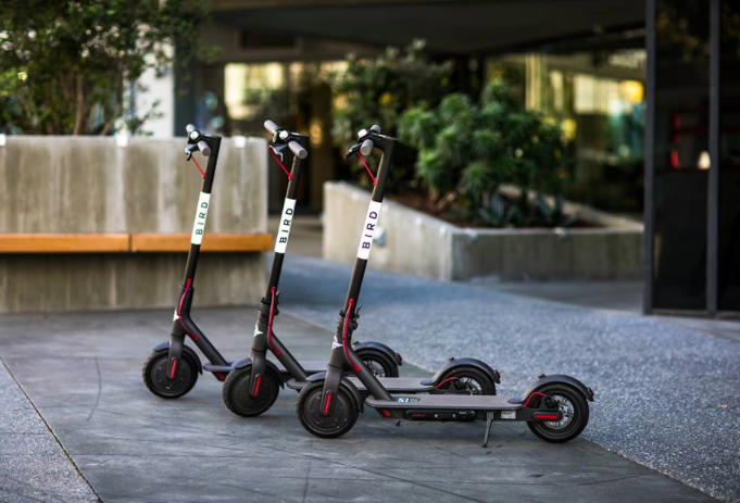 Image courtesy of Bird. Three scooters parked side by side.