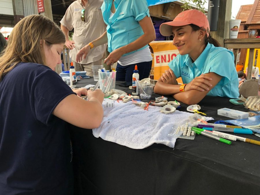 "Photos by Jonathan Garcia/Island Waves;  Adriana Chapa (right) watches Catherine Worley paint her oyster shell in the ""Paint your own oyster"" activity which was one of the many activities present at the event."