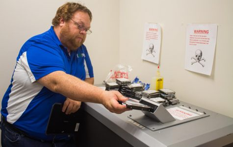 All photos courtesy of Kedran Wade/ISLANDWAVES -  IT's Security Analyst, Johnathan Cooper, demonstrates how to drop computer hard drives into hardware shredding machine.