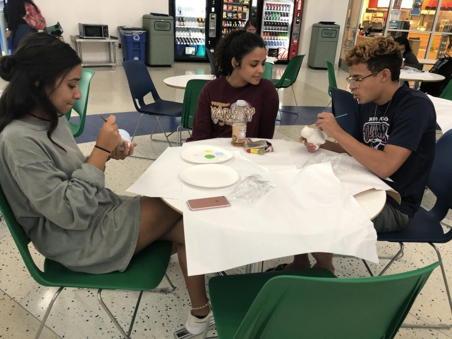 Photos by Jonathan Garcia/Island Waves- Freshman Kayla Vasquez (left) and Freshman Sebastian Szpack paint their own alebrijes while Junior Karla Vasquez is fascinated by the color choices.