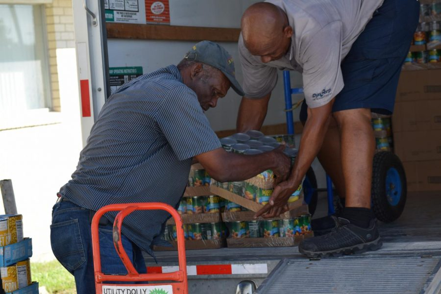 Raul Alonzo Jr./ISLAND WAVES - Alfred Williams (left), a steward at Brooks African Methodist Episcopal Worship Center, lifts a packet of canned food into a U-Haul bound for McAllen's Catholic Charities Humanitarian Respite Center Thursday, Sept. 26. The donations will be going to the migrants assisted by the center, as well as those waiting out their asylum claims across the border.