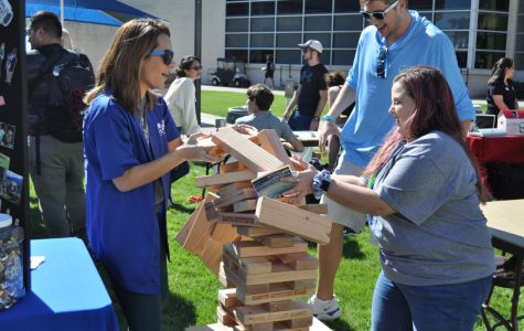 A game of giant Jenga topples at the Campus Activities Board table.