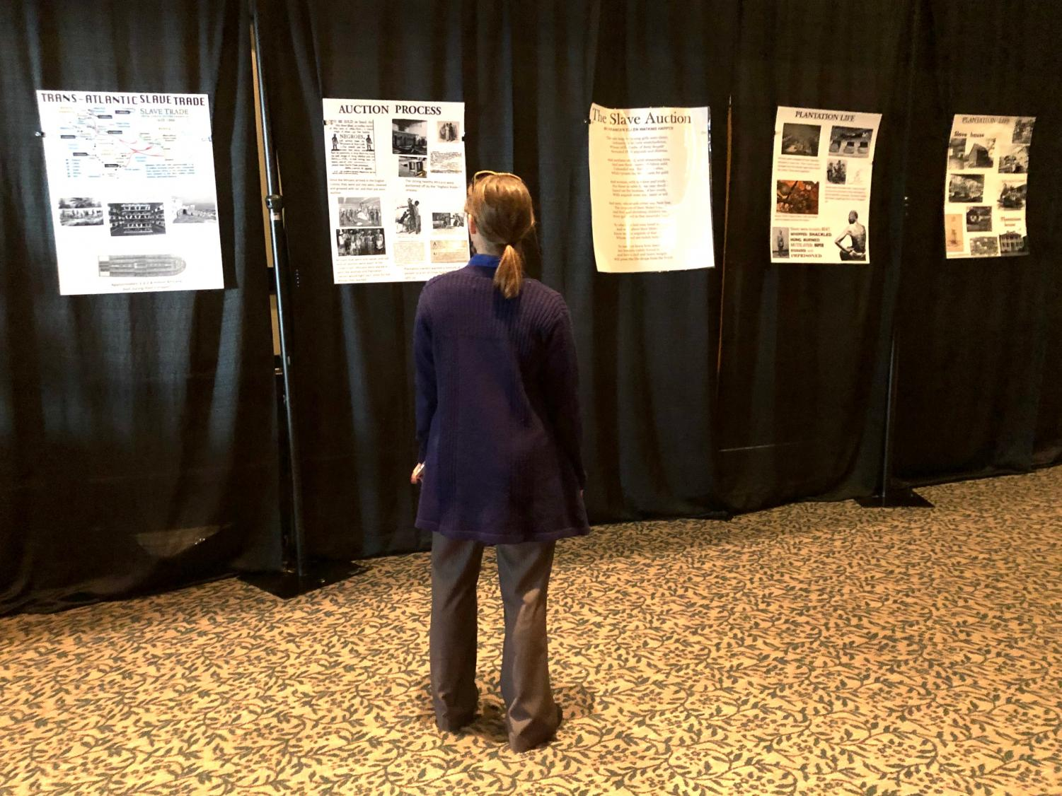 dee reads posters about the history of slavery in the U.S.